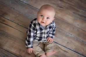 sitting like a little man on wood floor