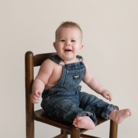 chubby baby in overalls sitting in chair
