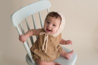 baby girl looking up sitting in chair