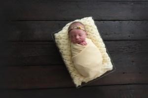 yellow wrap on barn wood newborn baby
