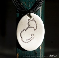 """""""Back to Front"""" pendant, 1"""" x 1.5"""" oval on multi-strand cord."""