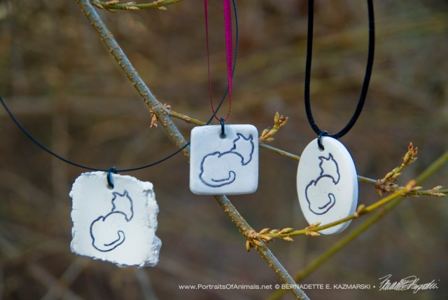 Three clay pendants.