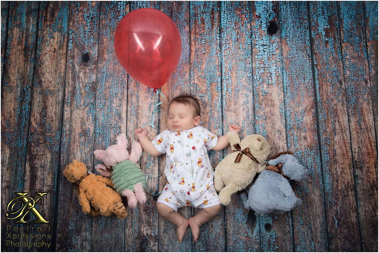 baby with teddy bears and red balloon