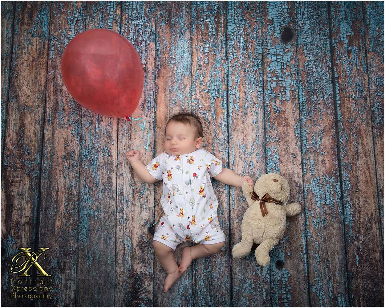 baby with red balloon and teddy bear