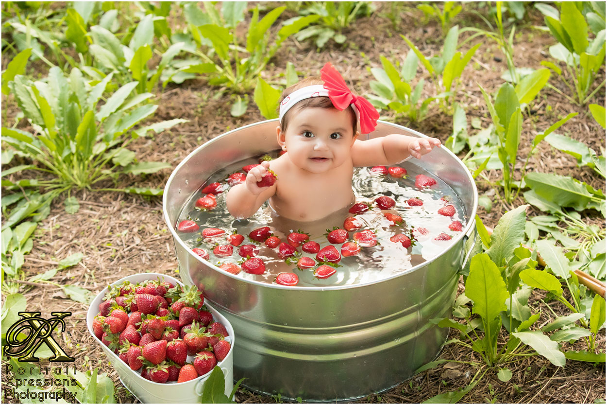 baby with bucket of strawberries