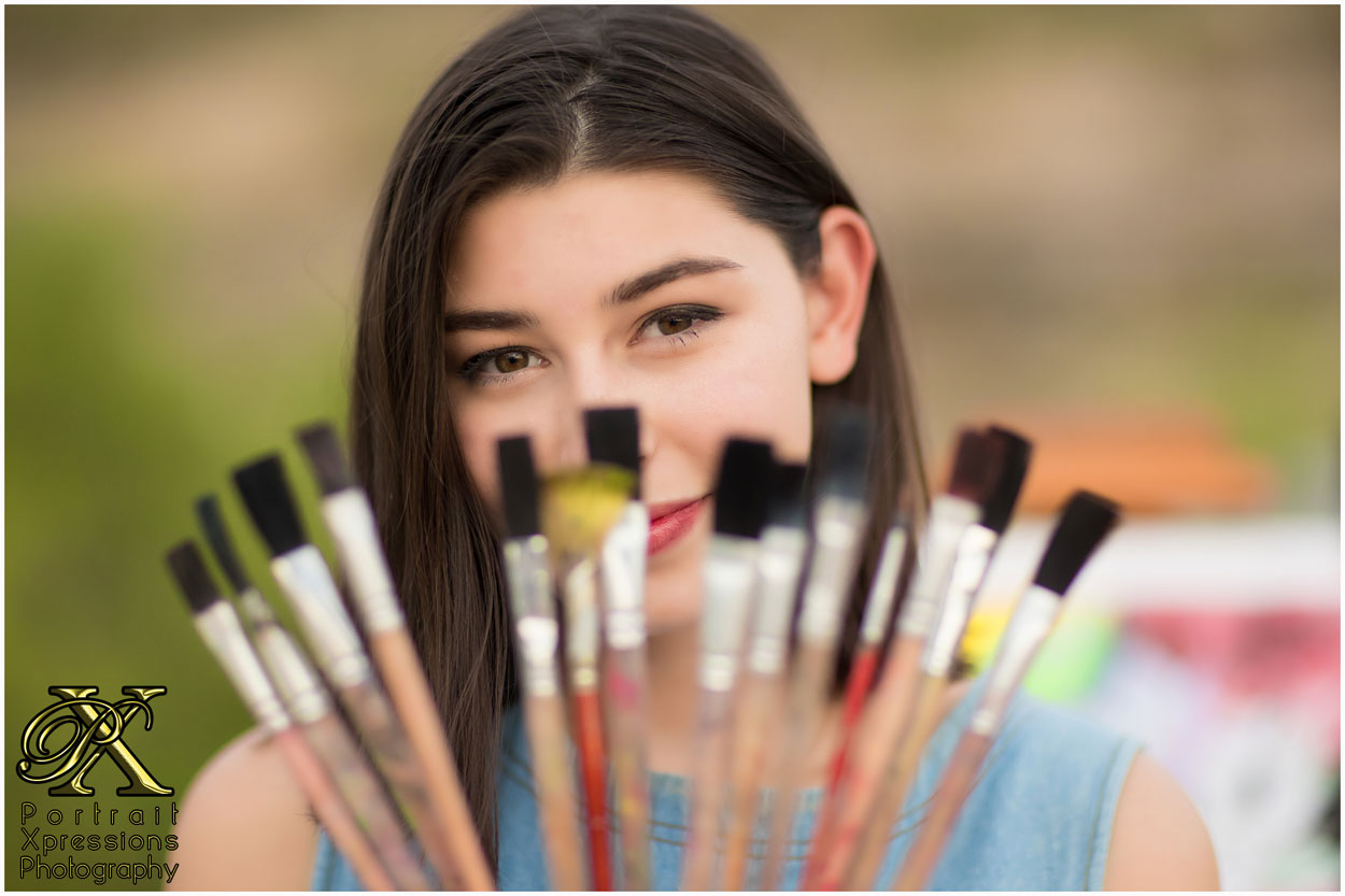 high school senior with paint brushes