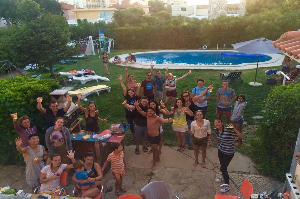 Happy people outside on the garden with swimming pool at the surf house in Carcavelos Portugal