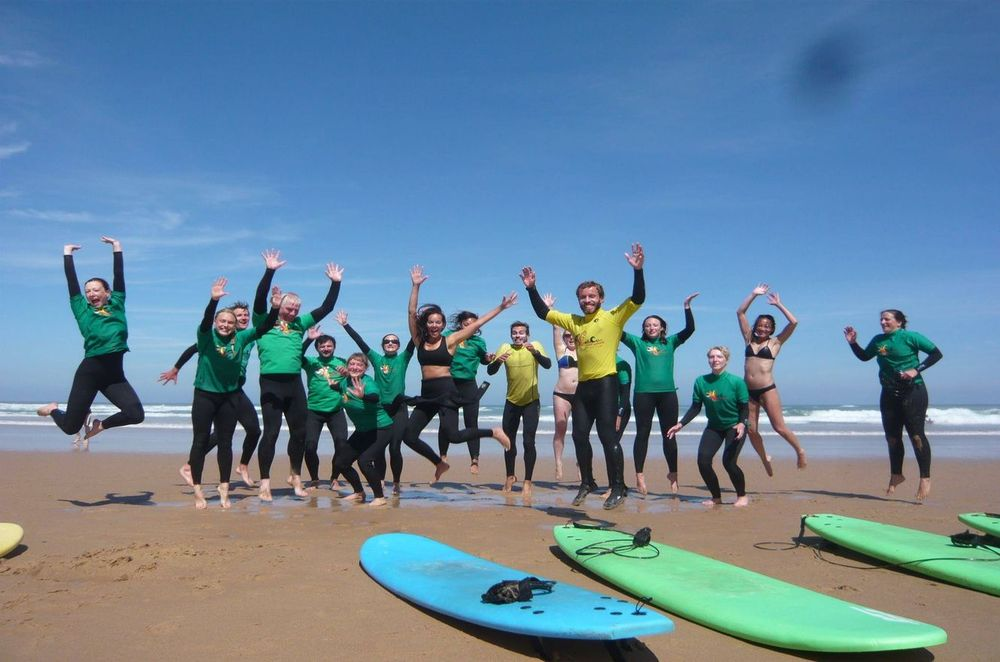 Happy people jumping on the surf lesson at the Odeceixe beach in Portugal