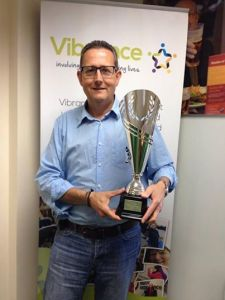 Vibrance Chief Executive, Paul Allen holds the Vibrance 25th anniversary celebration trophy
