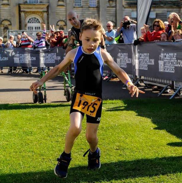 Inspirational eight-year-old boy with cerebral palsy completes triathlon