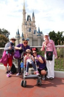 Rebecca Spooner, with family and Caudwell Children volunteers, at Magic Kingdom castle