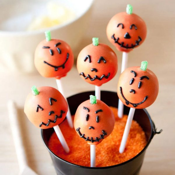 Six orange cake pops in a tub full of sanding sugar. Each of them are decorated with a different carved pumpkin face for Halloween.