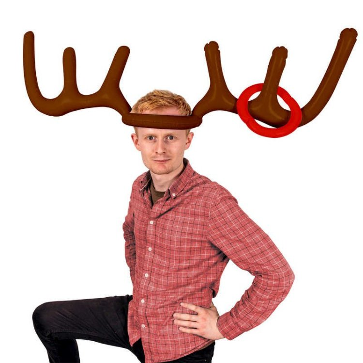 A man who is clearly trying not to laugh wearing inflatable antlers on his head. Someone has thrown a ring and it has landed on the antlers.