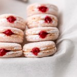 jelly donut flavored French macarons made with donut frosting, homemade raspberry jam and confectioner's sugar