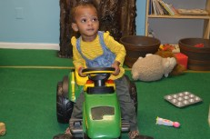 """Aria riding the tractor in the """"Farm"""" room!"""