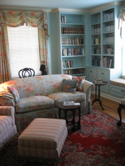 This library show off the homeowners antiques and fine rug; a comfortable sofa is slipcovered in rose printed linen.