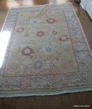 Pale Oushak carpet on the entry's dark wood floors