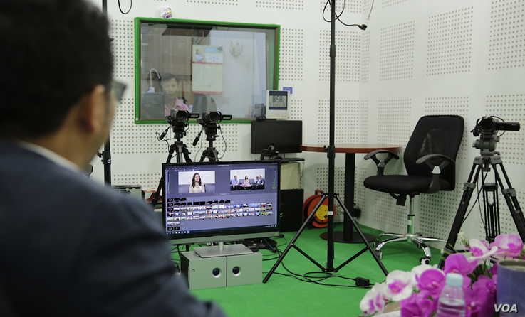 A studio engineer looks on as guest Chin Malin, spokesperson of Cambodia's Ministry of Justice, prepares for a VOD Roundtable program on judicial corruption, in Phnom Penh, Sept. 11, 2019. (Tum Malis/VOA Khmer)