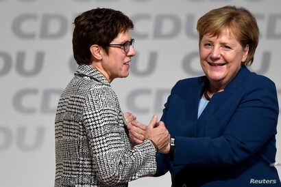Annegret Kramp-Karrenbauer is embraced by German Chancellor Angela Merkel after being elected as the party leader during the Christian Democratic Union (CDU) party congress in Hamburg, Germany, Dec. 7, 2018.