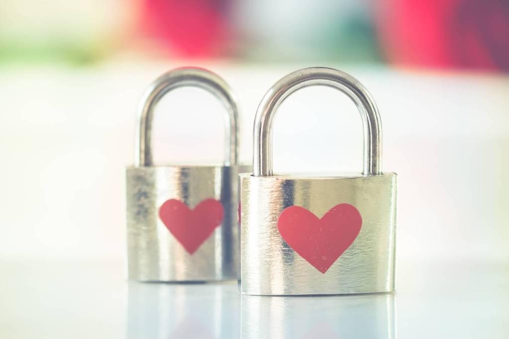 bokeh photo of two heart printed stainless steel padlocks