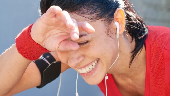 Young woman laughing and wiping away her sweat after jogging workout