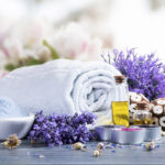 spa massage setting, product, oil on white table with flower background