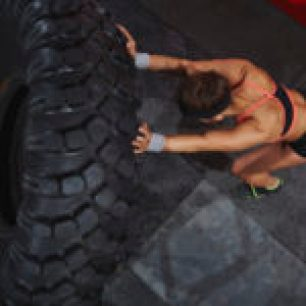 Strong sporty woman flipping tyre