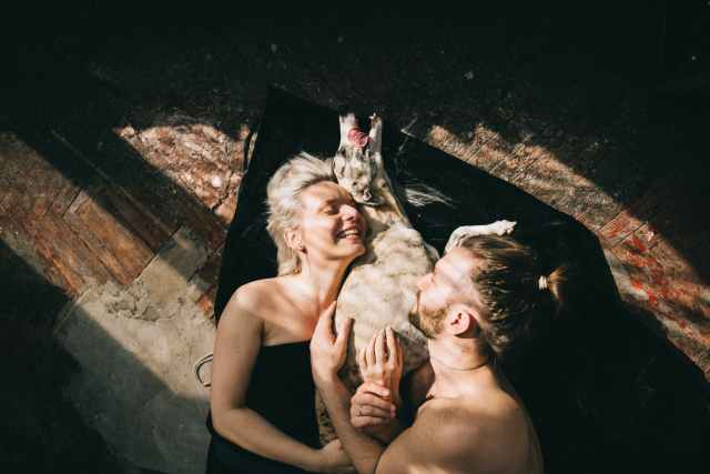 couple lying down and hugging their dog