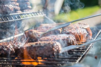 grilled meat assorted over flames on outdoor grill_man food example