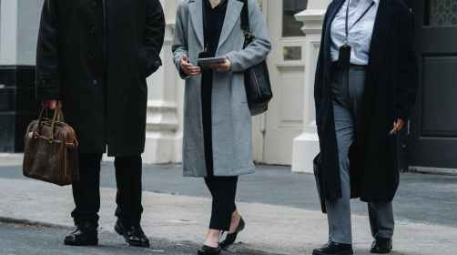 stylish businesspeople in elegant coats walking on street