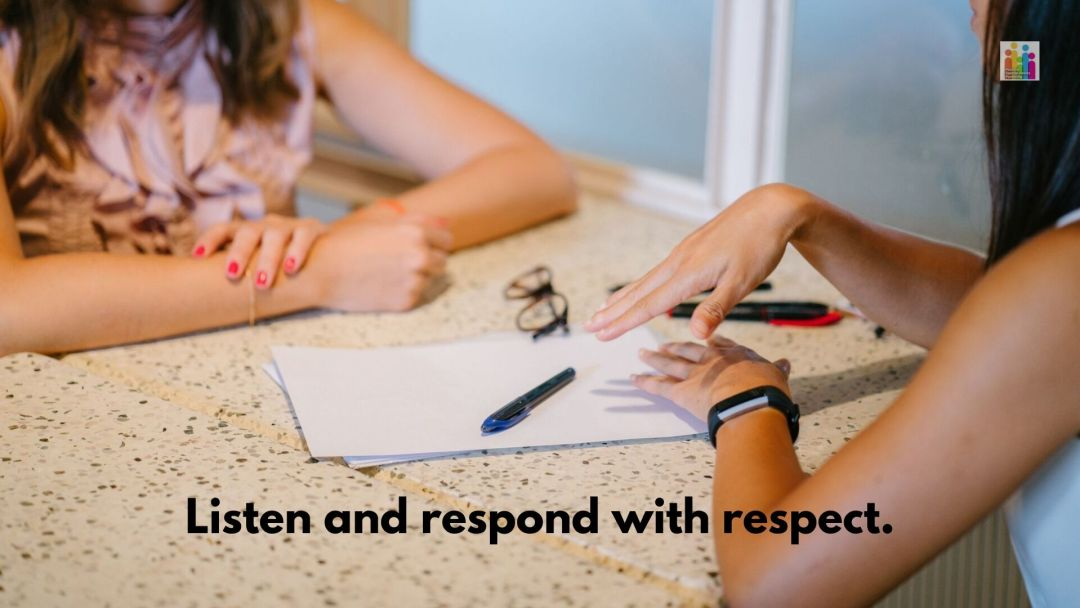 """Close up image of a table with paper, pens and a pair of glasses visible. Two women are sitting on either side of the table, with their arms visible as if in conversation. Text below the image reads, """"listen and respond with respect."""""""