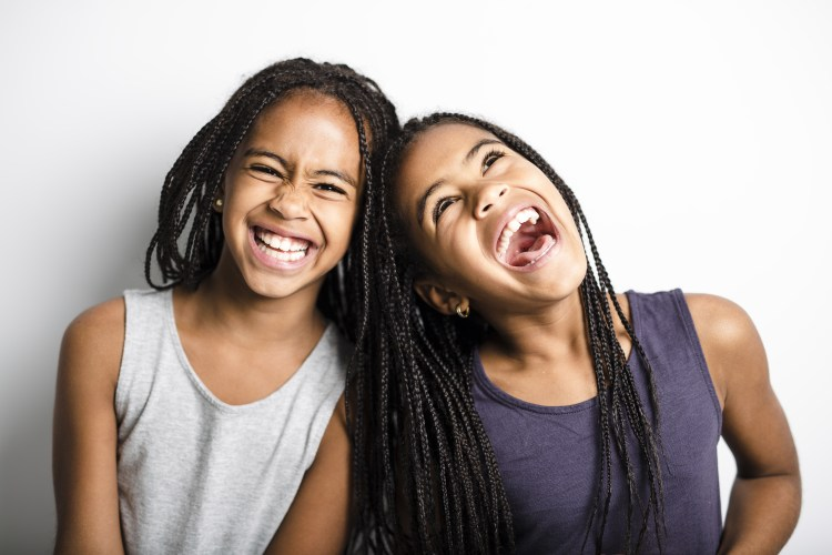 An Adorable african twin girls on studio gray background