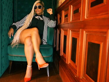 Picture of a woman sitting in a green chair with a black and white outfit and sunglasses.