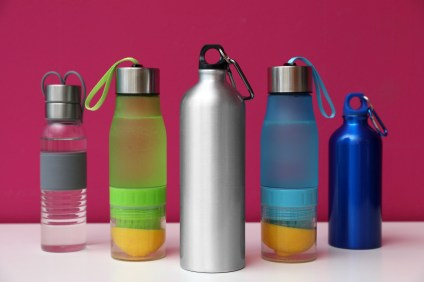 Different water bottles of various sizes with color background.