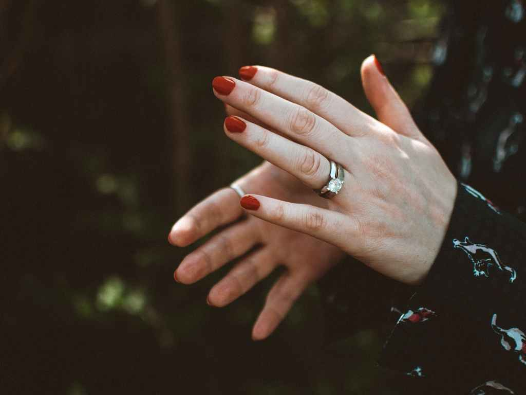 photo of person wearing silver diamond ring