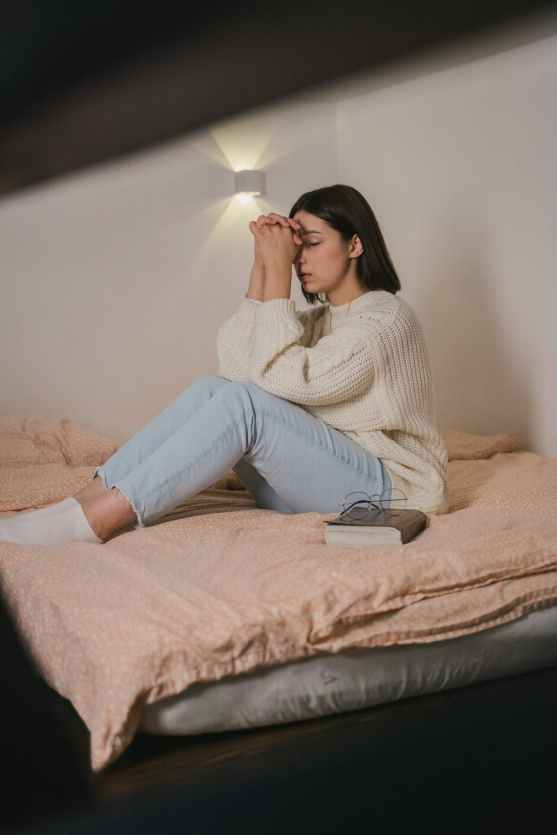 woman in white sweater and blue denim jeans sitting on bed