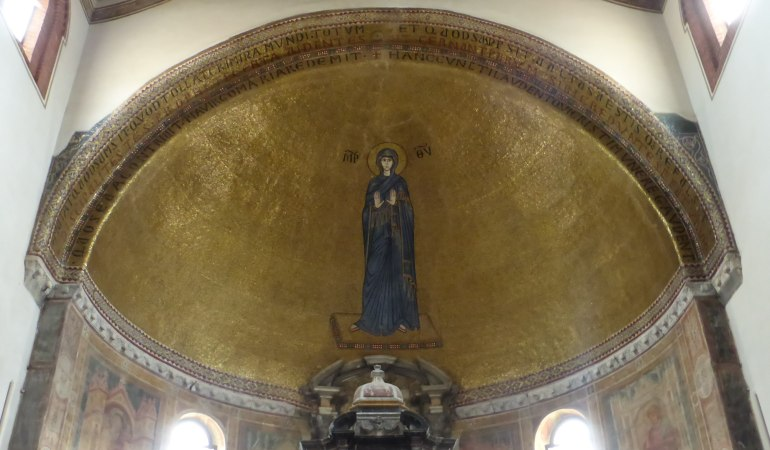 Gold mosaic of a madonna praying in the apse of the basilica