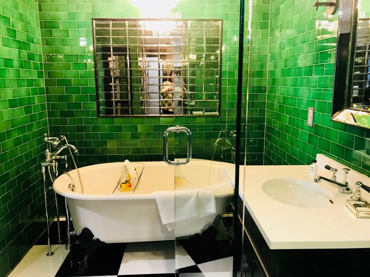 The bathroom in the Emerald Room features a claw foot tub and a walk in shower.