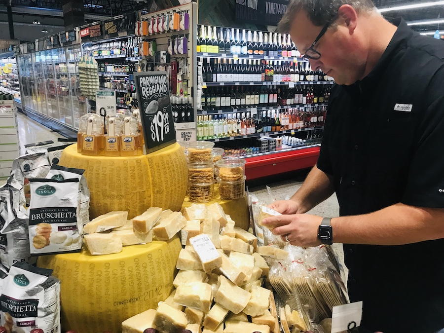 Steve selects a piece of Parmigiano Reggiano cheese at Whole Foods.