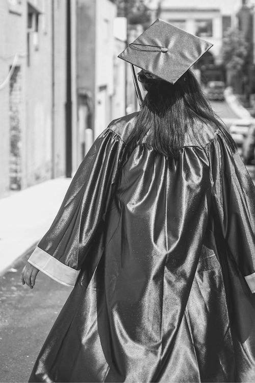 college graduate walking away to symbolize the role adulting plays in the job-hunting process