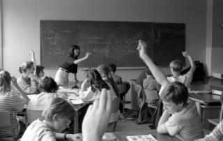 Classroom with a female teacher pointing to students. Several students with their hands raised to answer questions.