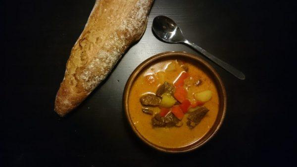 Bowl of goulash and a homemade flute