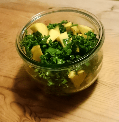 Kale and orange salad in a glass bowl