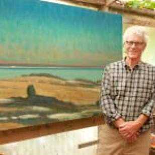 """Painter Allen Whiting in his studio with his work, """"Vineyard Sound From Menemsha."""" Photo: Martha's Vineyard Times"""