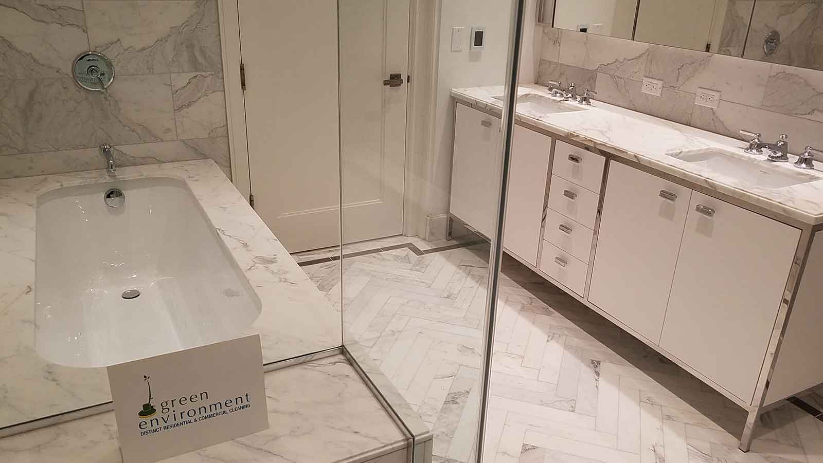 Marble bathroom vanity and tub after a post-construction cleaning by Post Green Cleaning.