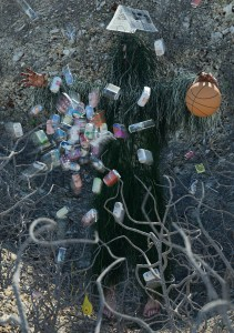 Man in a ghillie suit holding a basketball while cans are flying at him.