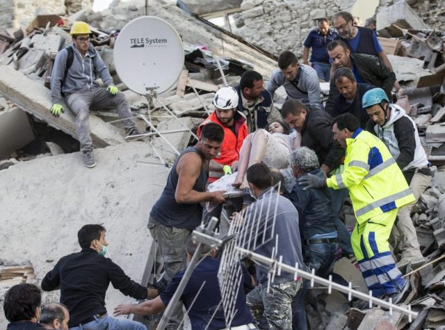 Rescuers carry an injured woman amid the rubble in Amatrice, Italy, on Wednesday.