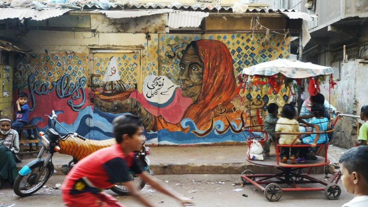 """In this Karachi mural, an old woman holds out a boat in her hand, a tribute to the area's history as an important shipping port. The text reads """"zindagi ke khel"""" (the games of life)."""