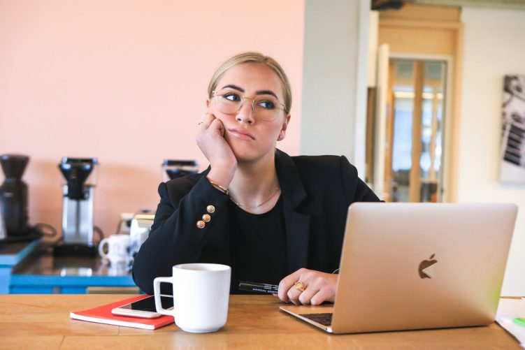 Woman at a laptop thinking