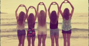 Teenage girls by the sea making heartshapes with their hands